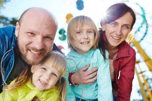 Poster Attraction parc Portrait of happy family looking at camera bending down, parents hugging two beautiful daughters close in sunlight during weekend together in amusement park