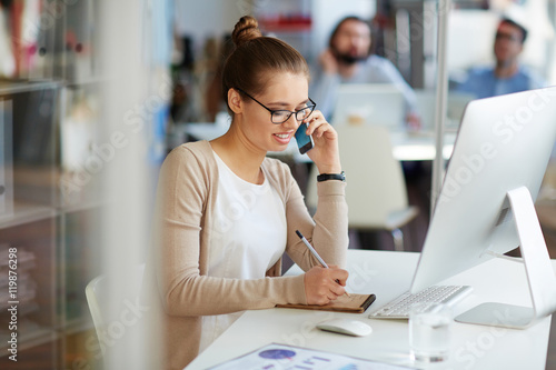 Foto  Young professional businesswoman working in public relations talking on phone wi