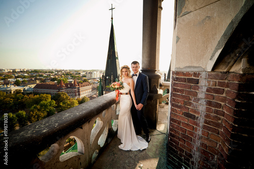 Happy wedding couple on old chuch's balcony Tablou Canvas