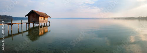 Photo Fishing Hut by Calm Lake at Sunset, Clouds Reflecting in the Water, Ammersee, Ba