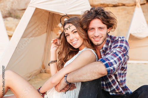 Photo  Couple sitting and hugging near wigwam on the beach