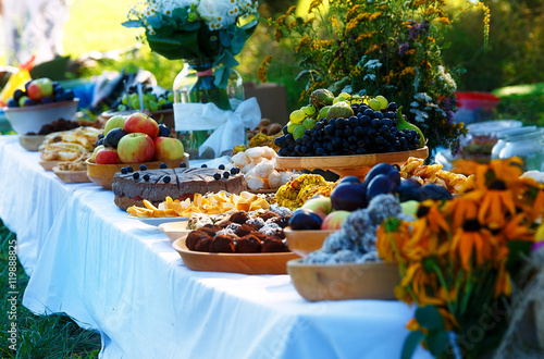 Fotografija Beautiful wedding feast in nature, abundance of meals on a table.