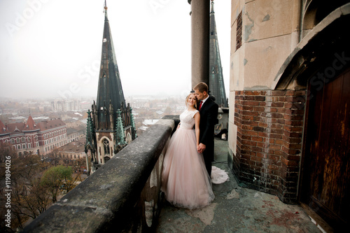Fotografie, Tablou  Beautiful bride and handsome groom on old balcony