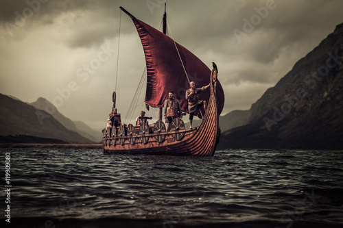 Fotografia  Vikings are floating on the sea on Drakkar with mountains on the