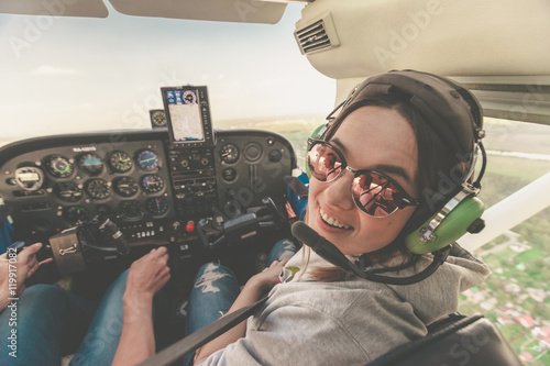 Canvas-taulu Confident female pilot with headset smiling in the private helicopter