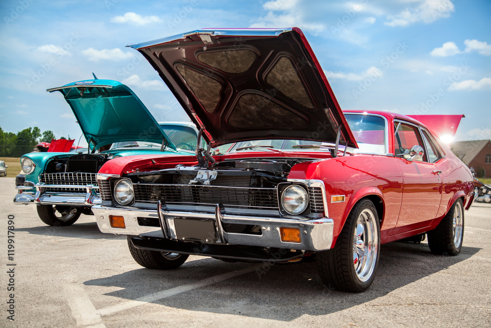 Fototapeta Two old American 70s customized muscle cars with the hoods open on the show