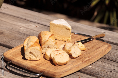 Fotografie, Obraz  French bread and triple cream brie cheese on a cutting board with a knife