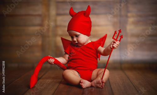 Fotografia funny baby in devil halloween costume on wooden background