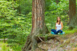 Young woman practices yoga in the wood.