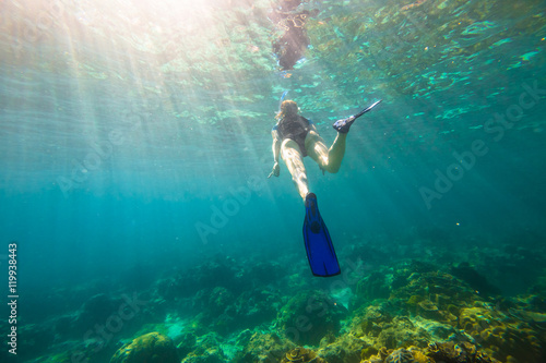 Young female snorkeling in tropical sea. Woman apnea swims in coral reef with sunbeams.
