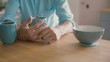 hands of a man playing with his wedding ring at the kitchen table. Slow motion