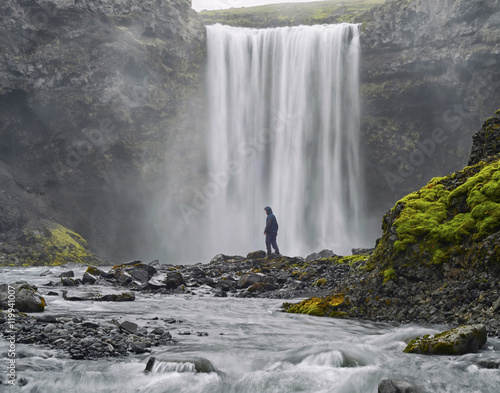 Küchenrückwand aus Glas mit Foto Wasserfalle A man dressed in black standing at the base of a waterfall . Beautiful vibrant panorama picture with a view on icelandic waterfall
