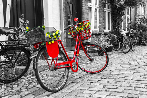 Deurstickers Fiets Retro vintage red bicycle on cobblestone street in the old town.