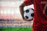 Fototapeta sport - soccer football player in red team concept holding soccer ball in the stadium