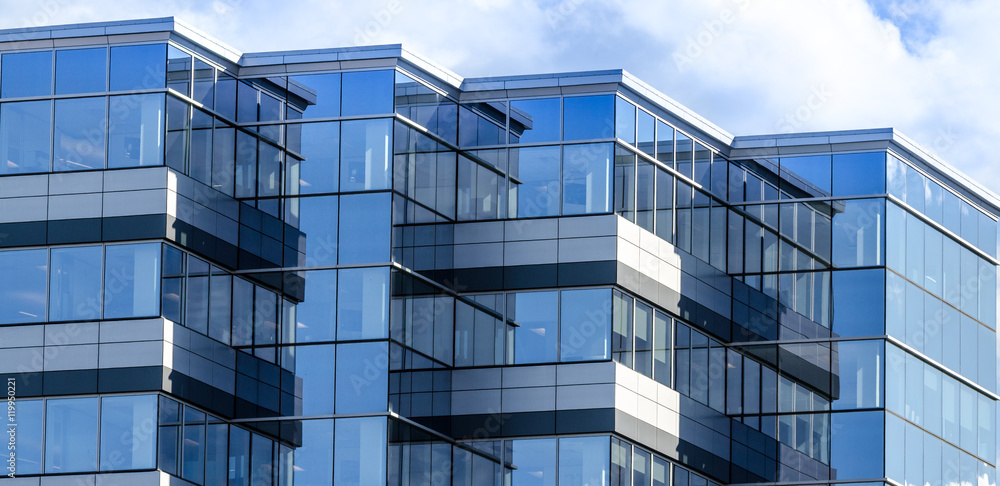 Fototapeta Lines, glass and reflections of modern architecture.  Glass panelled building of new office space in Moncton, New Brunswick.   New commercial real estate in the city.