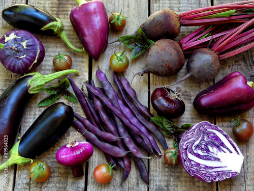 Foto auf Leinwand Gemuse purple vegetables on wooden background - eggplant, cauliflower, green beans, cherry tomatoes, basil, onion, cabbage, sweet pepper