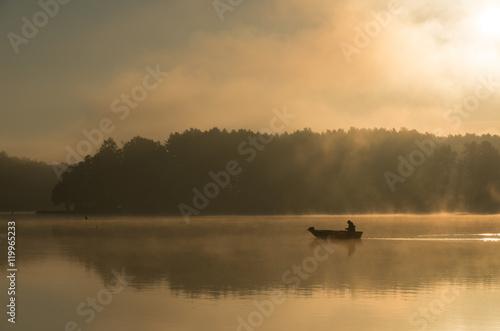 Człowiek wędkujący na łódce mglisty, złoty poranek.