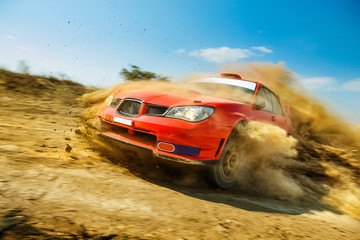 Powerful red rally car in the drift on dirt road