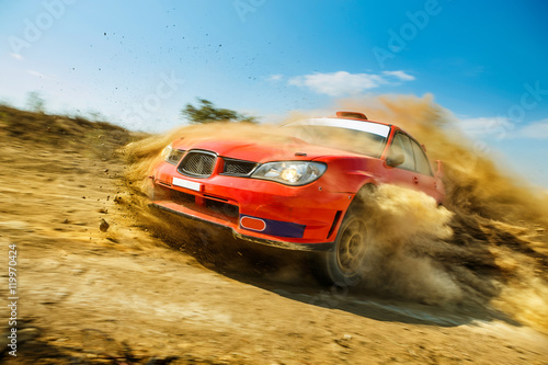 Foto  Powerful red rally car in the drift on dirt road