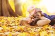 canvas print picture - Mutter mit Tochter liegen im Laub
