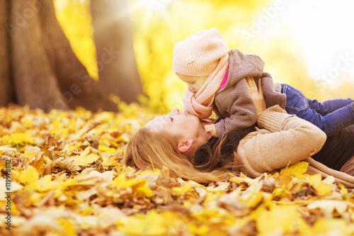 Poster Jaune Mutter mit Tochter liegen im Laub