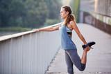 Athletic runner stretching legs before running