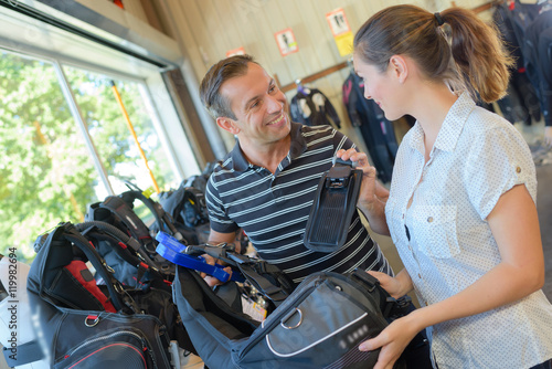 Fotografie, Tablou  Couple indoors with golf bags