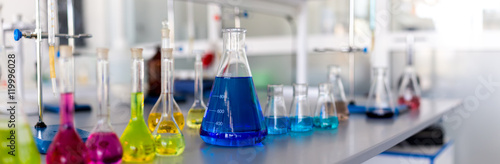 Fotografia  Laboratory table piled tubes with colored liquid, colored reagents in flasks and
