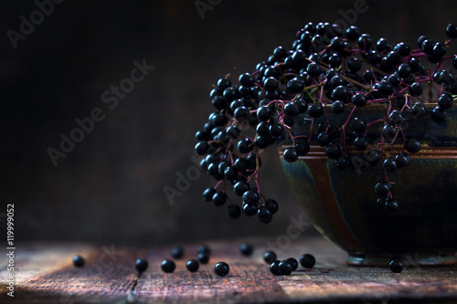 Black elderberries bunch (Sambucus nigra) in an old clay bowl, rustic wood, dark background