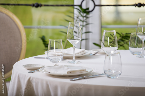 Empty glasses and plates installed in the restaurant, the restaurant served table, white tablecloth and wine