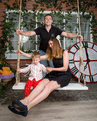 Man swinging his wife and baby son on teetering board at studio