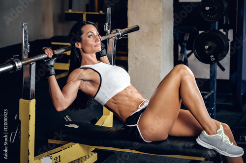 Sporty female lying on barbell stand.