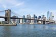 New York City skyline view of Brooklyn Bridge and Downtown Manhattan on bright summer afternoon