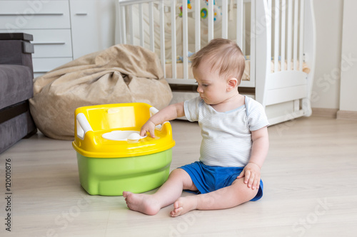 10 months old baby boy getting accustomed to using chamber pot Canvas Print