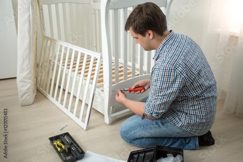 Plakat Mężczyzna gromadzi dziecko łóżko polowe po ruszać się w nowym domu