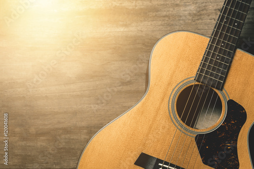 Foto  Acoustic guitar on vintage wooden background with sunlight effect filter