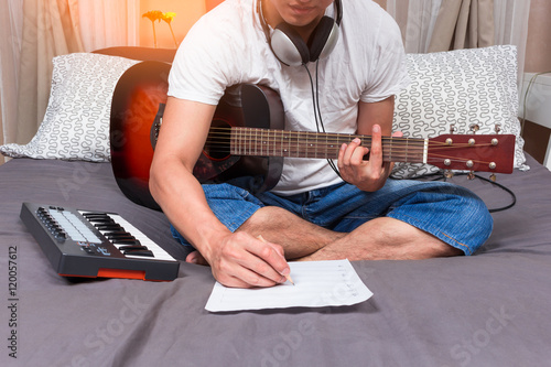 Fotografía  asian male composer, musician writing song & playing guitar on bed