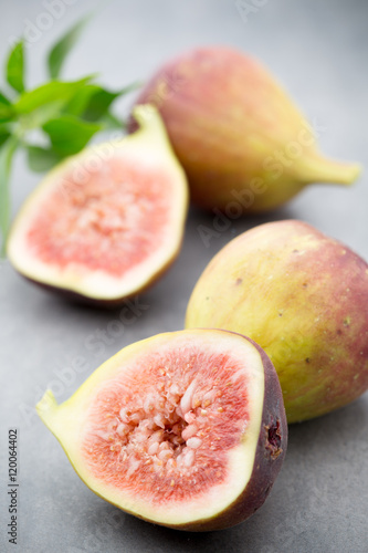 Whole Figs And One Fig Sliced In Half On Top Of A Gray Table