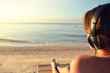 Young woman in headphones listening music and enjoying beautiful views sea, rear view.