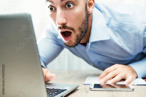 Photo uomo stupito davanti al monitor del notebook