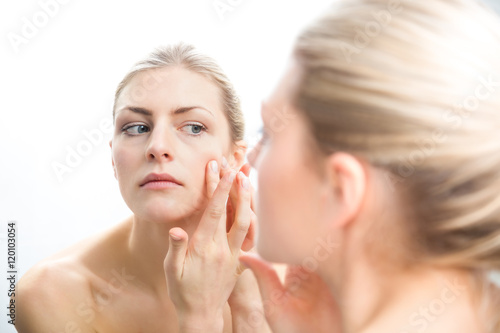 Fotografía  Young bare shouldered woman checking pimples