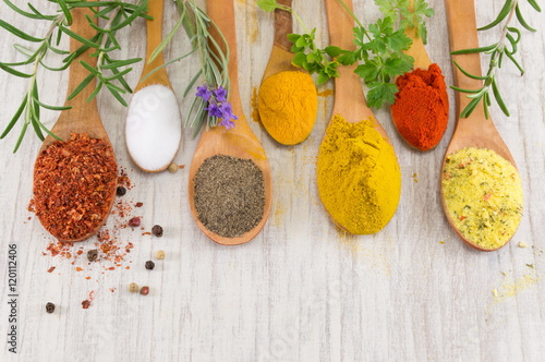 Photo  Various spices in wooden spoons on wooden table