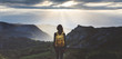 Leinwandbild Motiv Hipster young girl with backpack enjoying sunset on peak mountain. Tourist traveler on background valley landscape view mockup. Hiker looking sunlight flare in trip in Spain basque country Europa