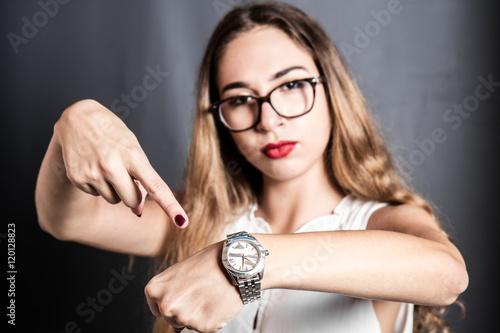 Fotografía  ragazza arrabbiata che indica l'orologio