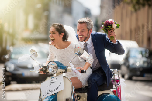 Fotografie, Obraz  Newlyweds having fun on a decorated vintage scooter