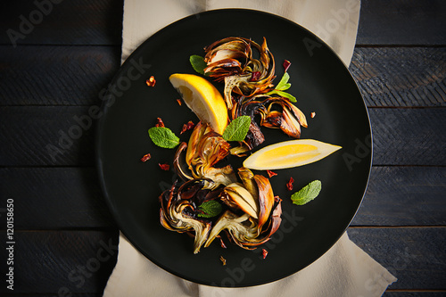 Photo Baked artichokes with spices on wooden background