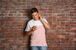 Handsome guy listening music on brick wall background
