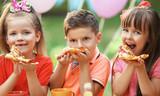 Children eating pizza in park - 120159810