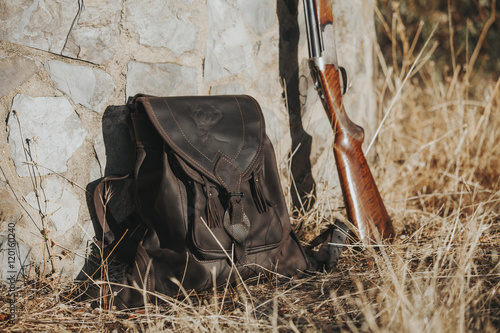 Fotobehang Jacht Leather bag on the pasture at the countryside close to a shotgun. Hunting concept.