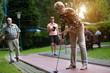 Eine Seniorin spielt Minigolf. Sie konzentriert sich auf den Schlag von dem Bahnrand aus. Im Hintergrund leuchtet die frühe Abendsonne durch die Bäume.